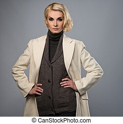 Elegant woman in white coat isolated on grey