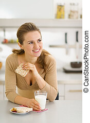 Young woman eating snacks in modern kitchen and looking on...