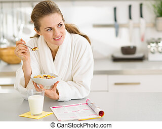 Thoughtful young woman in bathrobe eating breakfast in...