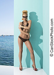 woman in bikini with sunglasses and hand on the arm