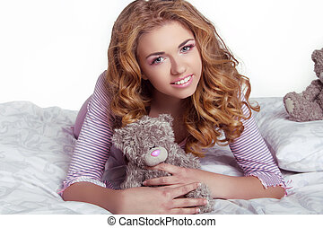Beautiful happy smiling young woman with teddy bear in bed...