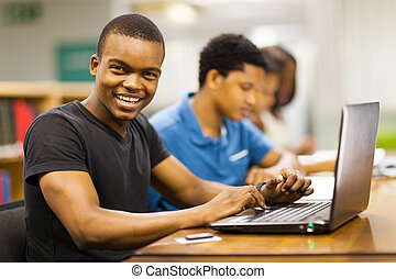 male african college student using laptop - happy male...