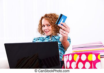 E-shopping - Woman with laptop and shopping bags showing a...
