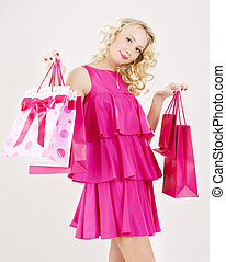 happy shopper - elegant blonde girl with pink shopping bags