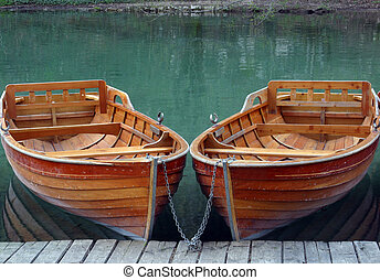 Rowboats parked in a row near a clear water lake