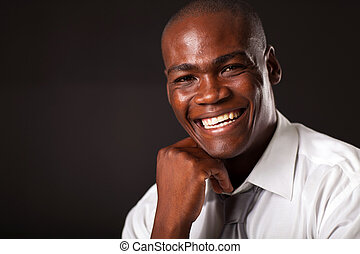 happy african american young man portrait over black...