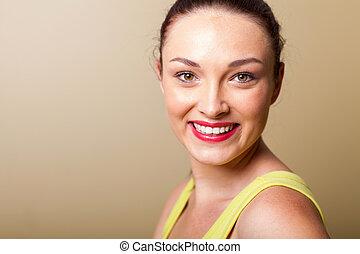 smiling beautiful young woman closeup portrait in studio