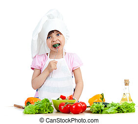 Chef kid preparing and tasting healthy food over white background