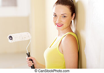 young woman with painting roller