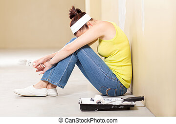 woman feeling tired after painting - young woman feeling...