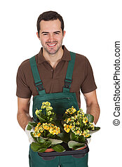 Happy young gardener holding flowers Isolated on white