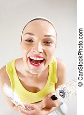 laughing young woman with paintbrush and roller