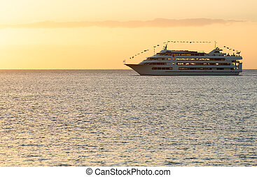 Cruise ship sails to setting sun