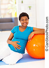 pregnant african woman on exercise mat at home
