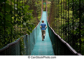 the great escape - young man running over a jungle bridge