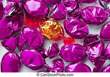 golden hard candy placed in between of purple hard candies -...