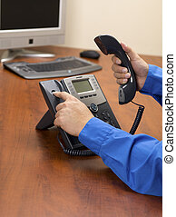 human hand disconnecting landline phone on wooden desk -...