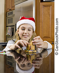 happy pre adolescent girl making gingerbread house - Happy...