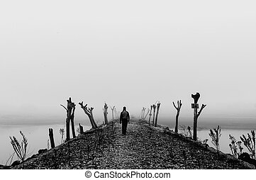 Man walking in a thick fog on wild desolate landscape Black...