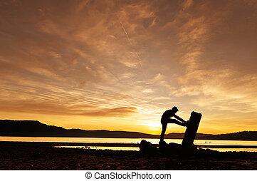 Man doing stretchings at the sunset