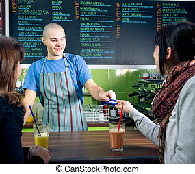 Paying with credit card - Bartender receiving credit card of...