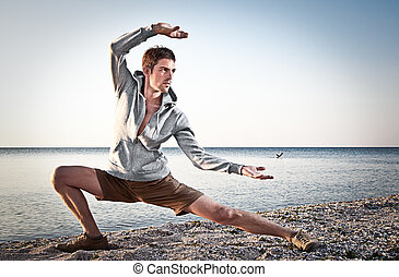 Young attractive man making Thai-chi movements on the beach...