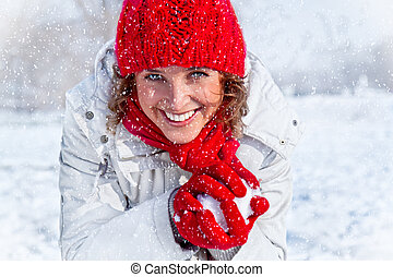Happy young woman playing snowball fight on the snow day....