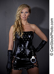 Dominatrix - Woman in leather outfit standing at the wall