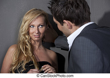 Flirting couple - Man flirting with a woman standing at the...