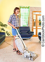 Young beautiful woman with vacuum cleaner at home. - House...