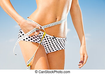 Woman measuring perfect shape of beautiful hips. Healthy...
