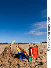 Beach toys in the sandy beach - Red watering can, plastic...