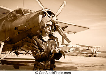 Portrait of beautiful female pilot with plane behind Sepia...