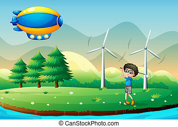 A boy playing golf in the field with windmills -...