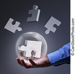 Male hand holding glass sphere with puzzle pieces - solution...