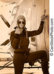 Beautiful girl in jacket standing next to war aircraft....