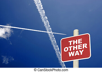 The other way sign with jet trails crossing a blue sky - The...
