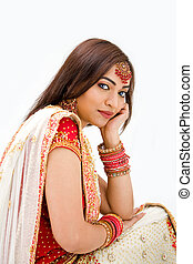 Beautiful Bengali bride in colorful dress day dreaming,...