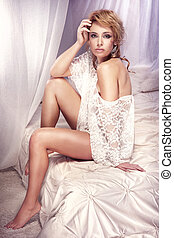 Photo of blonde beautiful woman posing in lace clothes on bed