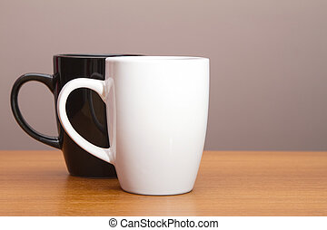 Black and white coffee mugs on wooden table