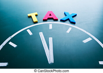 Time for tax concept, color word and clock on blackboard