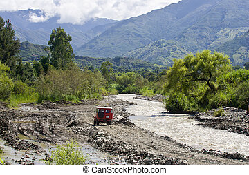 4-WD traveling river road in Andes - Red 4wd traveling on...