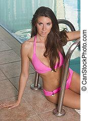 Beautiful big breasted bikini woman by a pool