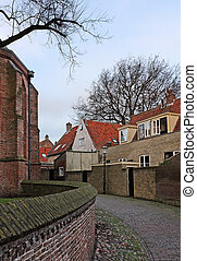Alley in old Dutch town Enkhuizen in late autumn, with part...