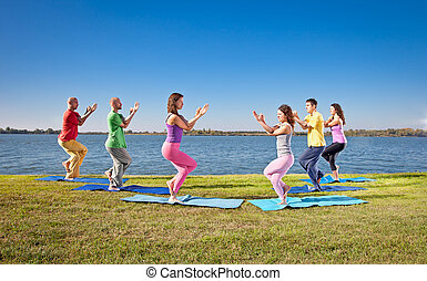 Tree couple , man and woman practice Yoga asana on lakeside...