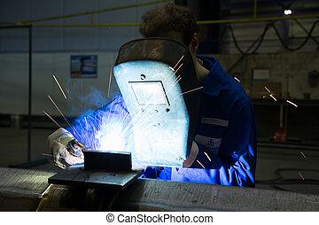 Worker with welding helmet welds steel