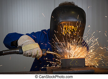 Man welding steel creating many sparks - Man with welding...