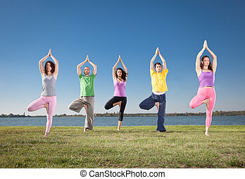 People in group practice Yoga asana on lakeside Yoga concept...