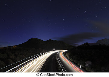 traffic at night in a motorway under the stars