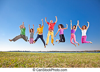 Happy smiling group of jumping people on banch of lake